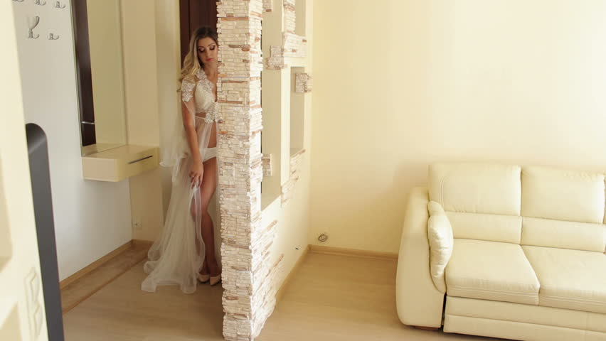 Sexy erotic girl in lace underwear is slowly walking along the beautiful modern apartment.