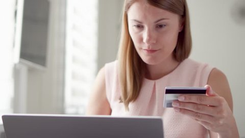 Young pretty woman sitting at home. Shopping online with credit card on laptop. Consumerism internet online purchases