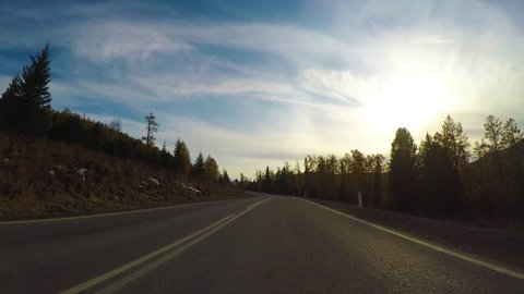 Driving down a quiet rural highway during the day in autumn. Seminsky pass, Chuysky tract, Siberia, Russia.