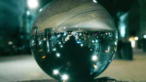 Night city street traffic reflecting upside down in the glass ball