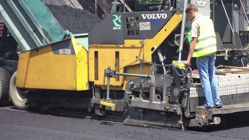 Kiev, Ukraine - June 19, 2017: Road construction. Workers applying new hot asphalt using road construction machinery and power industrial tools. Roadworks repaving process. | Shutterstock HD Video #32730292