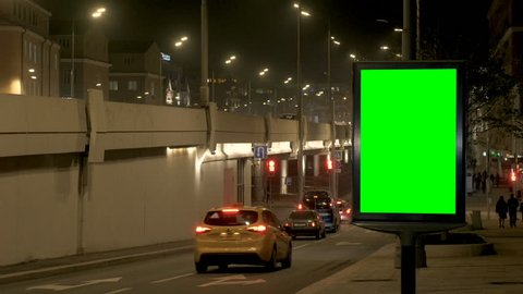 close citylight box with green screen on roadside at underpass wall against cars driving to tunnel at night