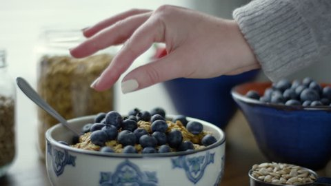 Woman Picks Up A Single Blueberry, To Eat, From Her Bowl Of Granola, Slow Motion, 4K