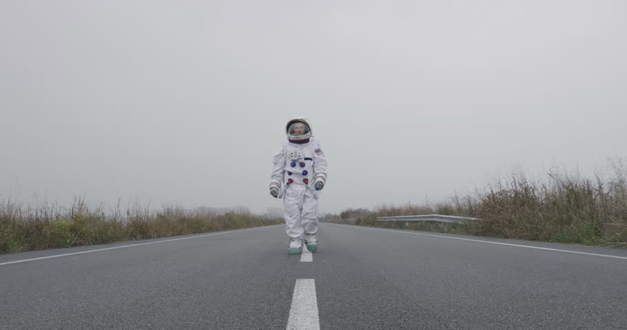 An astronaut just landed from space, on the new planet, walks in the middle of a road to explore the new world and live there. Concept of: success road, dreams, astronaut, inspiration.