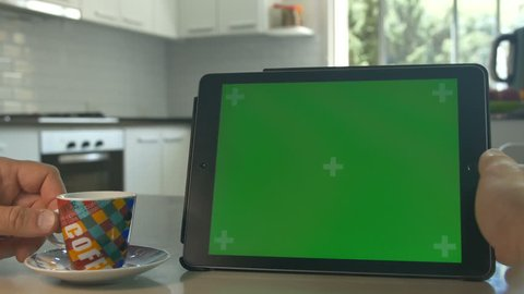 Tablet held by hands. Green screen Chroma Key. Close up. Tracking motion. Horizontal. POV, modern kitchen, day, Swipe left / right animation. Coffee / Tee