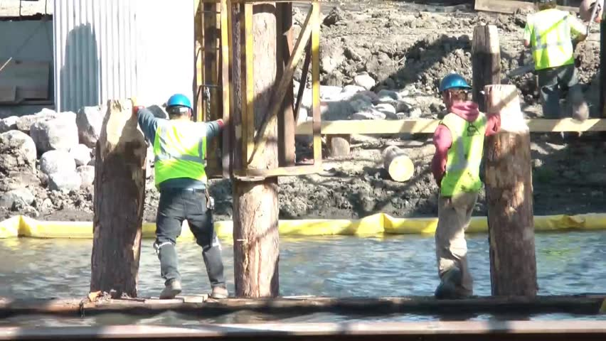 Men at work on river constructing new bridge wearing blue hard hats and standing on object in middle of water.