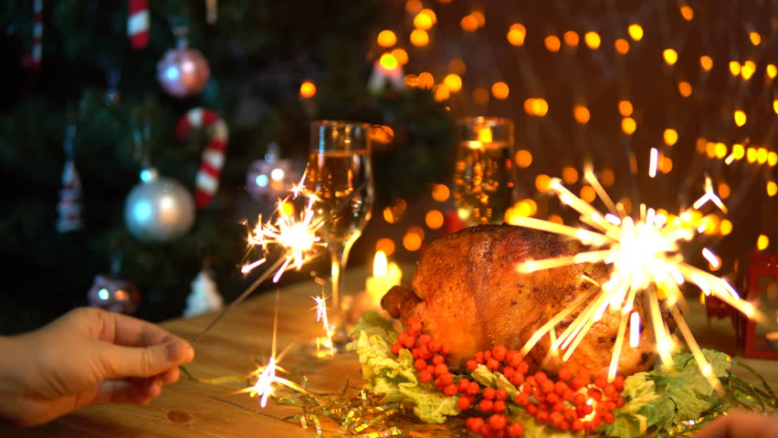 4k0019two people waving sparklers over a festive table with fried bird and glasses of champagne against the yellow electric lights