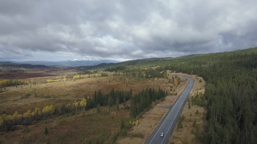 Aerial 4k drone footage view of a Canadian landscape with a scenic route in the country side during an Autumn season. Taken in the interior British Columbia, Canada.