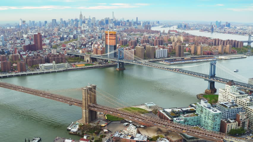 Aerial view of the Brooklyn and Manhattan Bridge in NY. Cityscape and famous skyscrapers in the Financial District and Midtown Manhattan. Shot from a helicopter. | Shutterstock HD Video #32798560