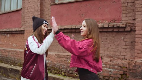 Two beautiful young hipster girl giving high five in urban background slow motion
