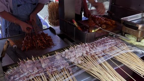 Cook preparing traditional Chinese street food in Lanzhou, Gansu province, China, Asia. Market with stalls and shops selling Asian food. People at work in restaurant kitchen