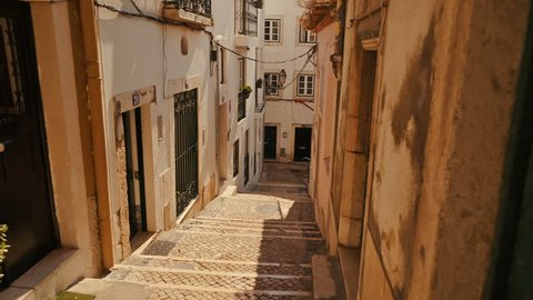 Walking along the picturesque streets of Alfama, the oldest district of Lisbon, Portugal. Alfama boasts many historical attractions along with Fado bars and restaurants.