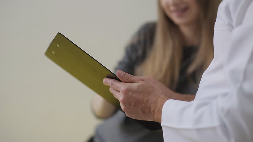 a doctor examines a pregnant woman and writes to the medical appointment card for treatment