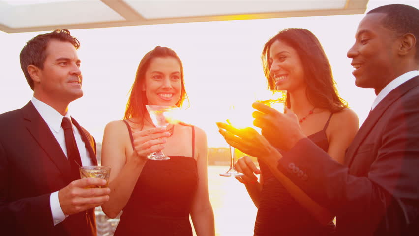 Young multi ethnic pretty girls drinking with attractive men at sunset outdoor party with lens flare. shot on RED EPIC.