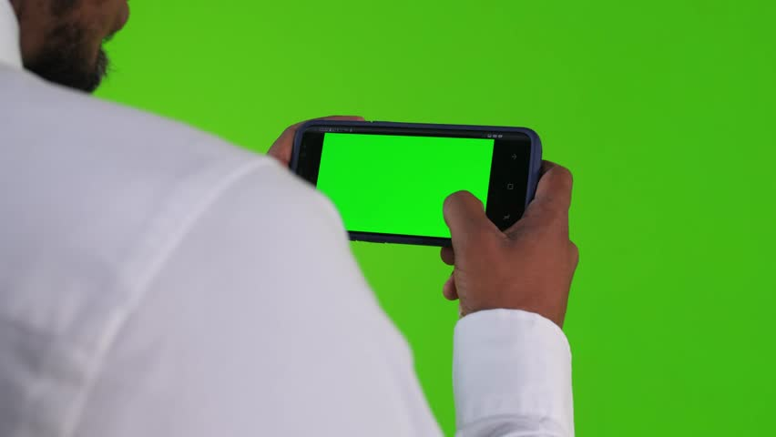 Over the shoulder, texting or using an app in a phone by a young businessman over a green screen. long shot. | Shutterstock HD Video #32889892