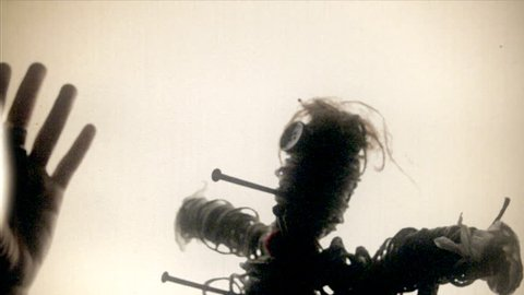Fake 8mm amateur film: the scay silhouette of a cursed voodoo doll, pierced by big rusty nails, over a white background.