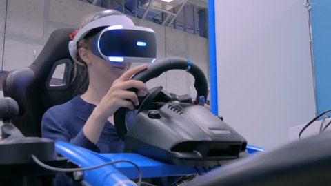 Young woman using virtual reality headset and playing in car drive simulator at technology exhibition. Future and video game concept