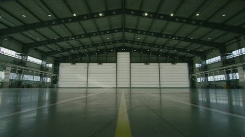 Hangar for aircraft with large open gate at sunny summer day. Large aircraft hangar open the gates