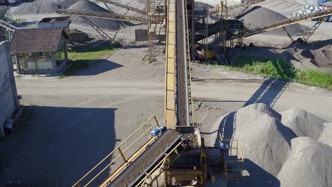 Aerial view, camera tracking conveyor belt that transporting rocks and soil while dropping on heap, stone crusher machine, mixer truck leaving, plant for sand and gravel production, building industry