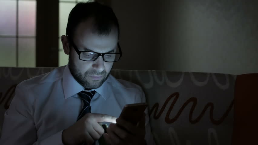 Online banking with smart phone. Handsome man on-line shopping with credit card using smartphone at night time in home.. The businessman made an electronic successful payment, sitting on sofa at night | Shutterstock HD Video #32932432