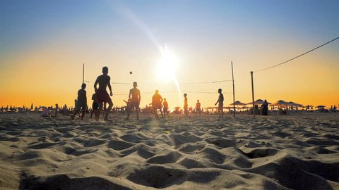 silhouette of volleyball players on the beach at sunset, cinematic steadicam shot