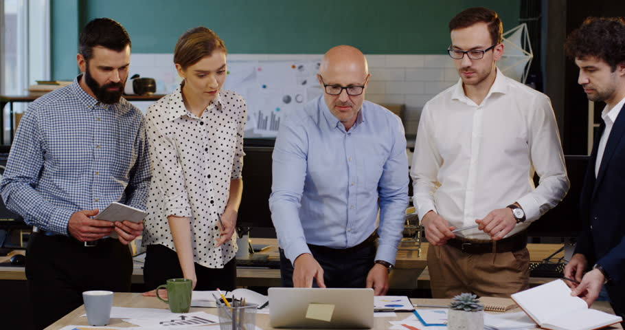 Young group of office workers leaning on a table with documents, charts, graphics and financial reports on it while discussing their business project and strategy with their boss. Inside of modern | Shutterstock HD Video #32941648
