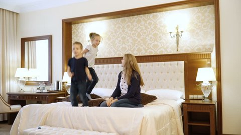 Scene Shows Young family Jumping on Bed in Room. Mom, Dad and children of European Appearance. Concept of Happy Family Life, Success, Entertainment, Advertising Hotels or Bed Linen