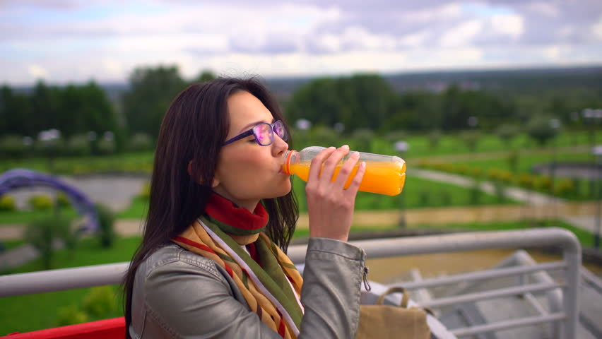 Young beautiful woman girl drinking orange juice from the bottle outdoors at summer park. A genuine fruit fresh juice that is good for body. Concept of healthy drinks diet vitamins natural nutrition