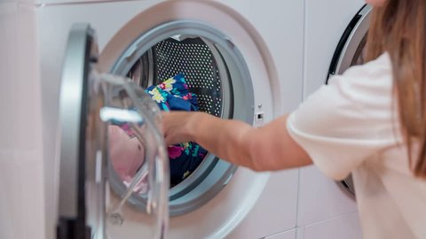 Womam is gently putting colourful laundry into washing machine. Meanwhile clothes are drying and spinning in the dryer.