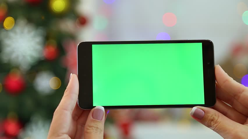 Closeup of female hands holding black modern smartphone in hands at glowing Christmas home interior. Adult woman uses digital device with blank green screen. Real time full hd video. | Shutterstock HD Video #32983426