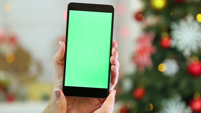 Closeup of female hands holding black modern smartphone in hands at glowing Christmas home cozy interior. Adult white woman uses digital device with blank green screen. Real time full hd video. | Shutterstock HD Video #32985010