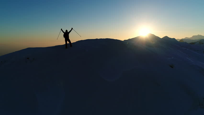 Aerial - Flyover silhouette of adult male mountaineer with trekking poles that raises arms on top of snowy mountain after successful climb in winter season | Shutterstock HD Video #32996872