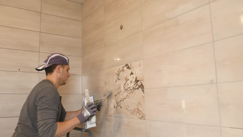 Man putting seams of beige tiles on the wall | Shutterstock HD Video #33004882