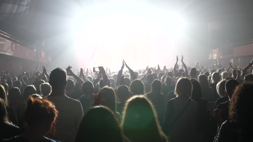 Clapping spectators - cheering concert crowd fan people in stage bright light lumiere | Shutterstock HD Video #33009652