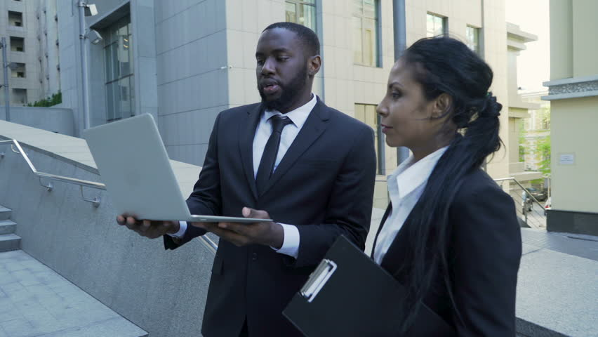 Man and woman looking at laptop outside building, attorneys, brand new evidence | Shutterstock HD Video #33019492