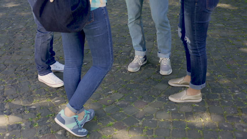 Group of male and female teenagers wearing jeans and sport shoes communicating | Shutterstock HD Video #33020650