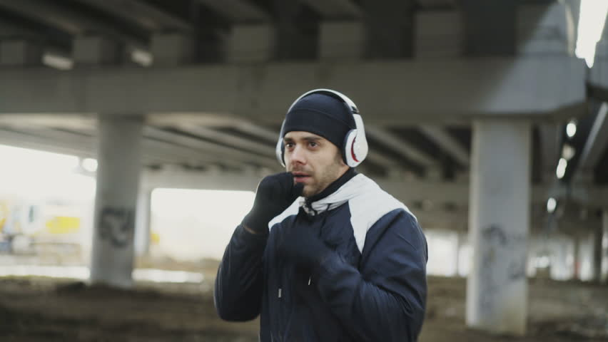 Dolly shot of sportive man boxer in headphones training punches in urban location outdoors in winter   Shutterstock HD Video #33024940