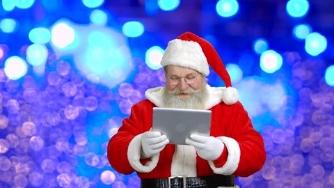 Santa's wishing merry Christmas through the tablet. Santa with tablet in front of a blue background.