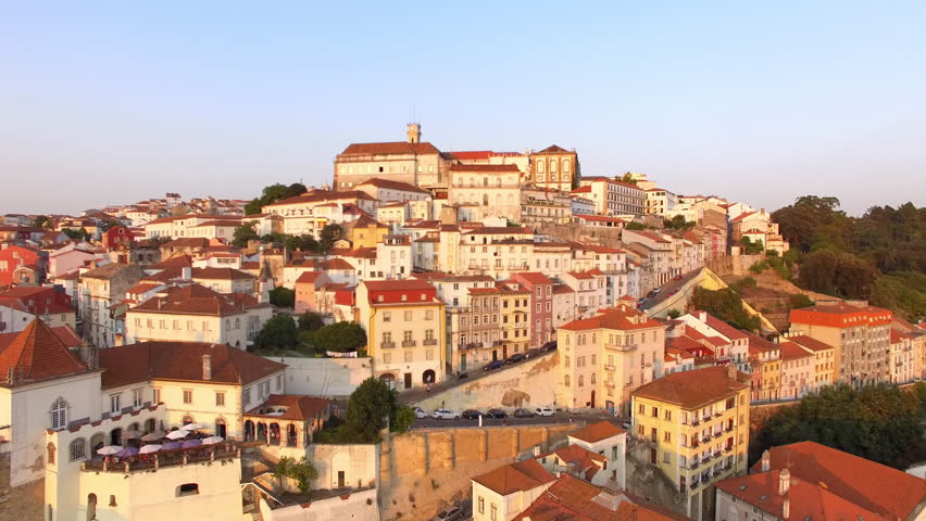 Coimbra, Portugal, aerial view of cityscape including the famous University of Coimbra and Clock Tower at sunset.