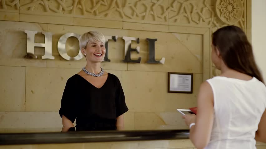 Tourist comes to the reception in the hotel and gives her passport. Receptionist politely checks her passport and gives her the form to fill. | Shutterstock HD Video #33056812