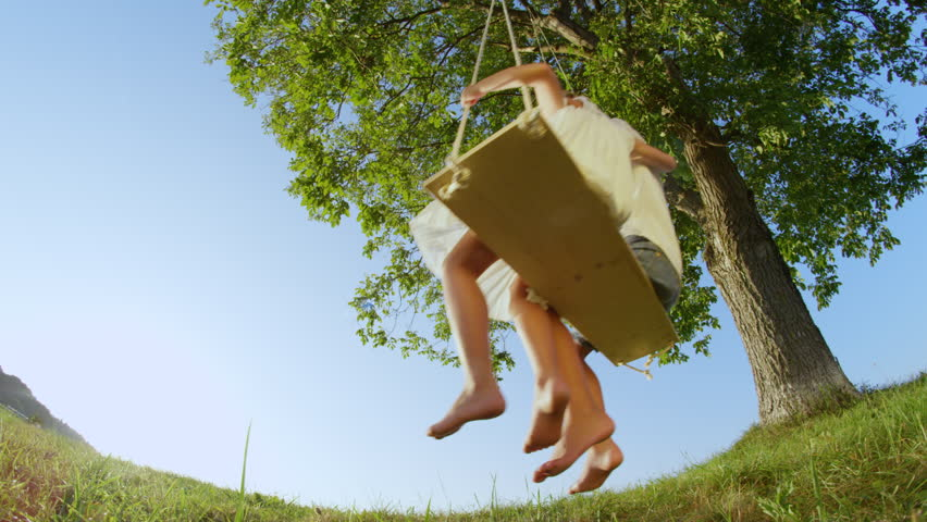SLOW MOTION LOW ANGLE: Cheerful couple of kids embracing on big swing. Happy little brother and sister have fun swaying on swing in sunny spring. Smiling boy and girl hugging and swinging under a tree