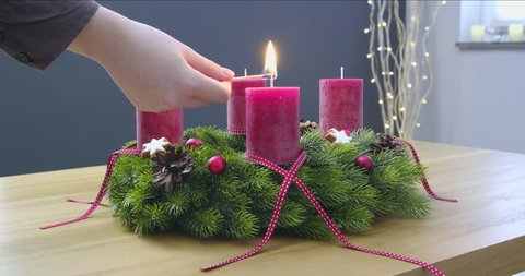 First Sunday of Advent - a young woman is lighting the first candle of the advent wreath
