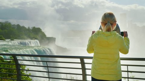 A woman looks at Niagara Falls through a coin operated binoculars. Tourism in the USA concept