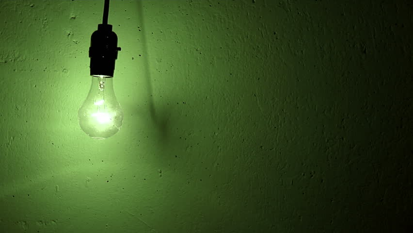 lightbulb swings and flickers against a green textured wall