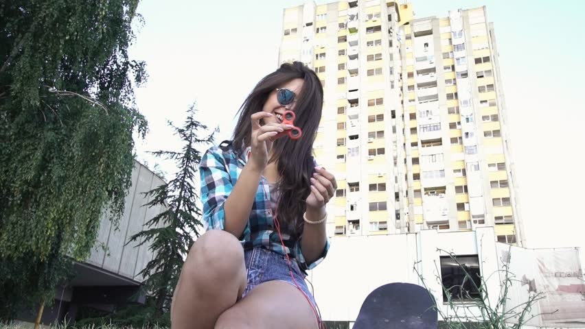 SLOW MOTION: Cute hipster girl sitting on pavement playing with fidget spinner | Shutterstock HD Video #33079621