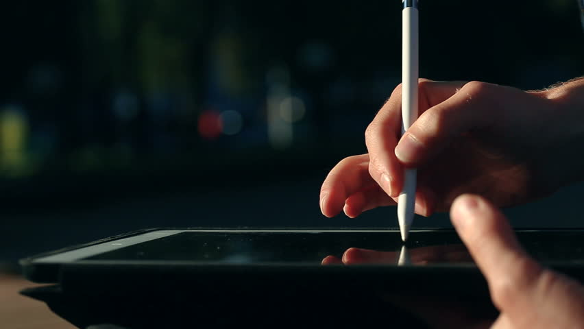 Extremely closeup shot of painter's hand drawing a sketch on tablet using stylus at park.  | Shutterstock HD Video #33082756
