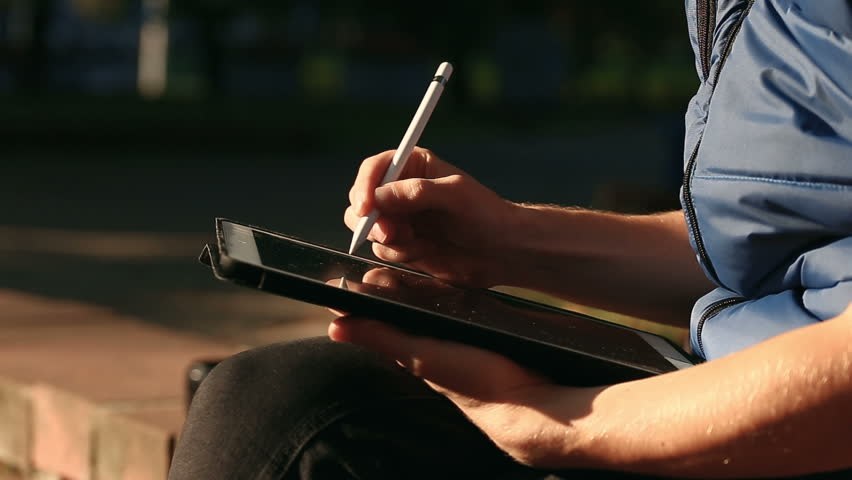 Closeup shot of designer's hand drawing and scaling On Tablet using stylus at park | Shutterstock HD Video #33082789