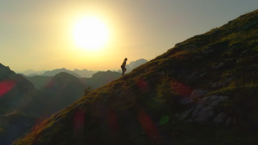 AERIAL SILHOUETTE: Camera flying along a contour of young woman hiker walking up a grassy, rock-specked hill at golden sundown. Female hiker ascending a mountaintop in stunning amber summer evening.