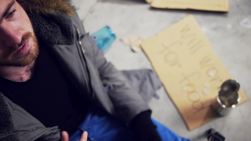 homeless man lighting a cigarette