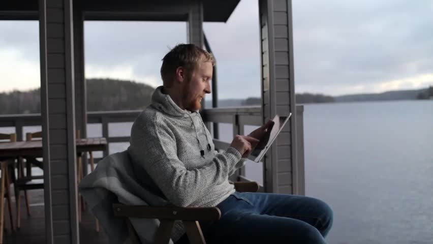 Man with a tablet sits on the terrace of a house on the lake | Shutterstock HD Video #33111565